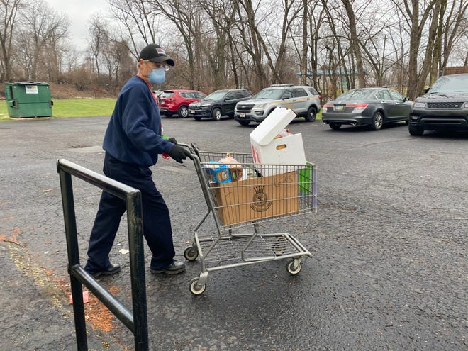 Rick Annen, 60, of Canton, pushes a cart of donations during the Salvation Army's Christmas distribution on Monday,
