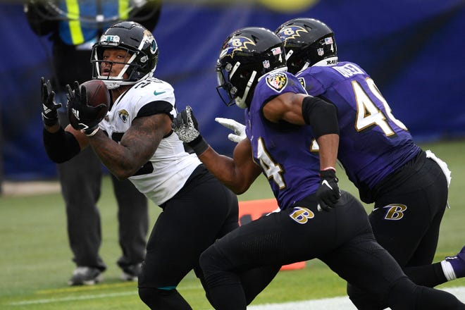 Jacksonville Jaguars running back James Robinson, left, hauls in a touchdown catch on a pass from quarterback Gardner Minshew II as Baltimore Ravens cornerback Marlon Humphrey (44) and linebacker Patrick Queen (48) defend Sunday, Dec. 20, 2020, in Baltimore.