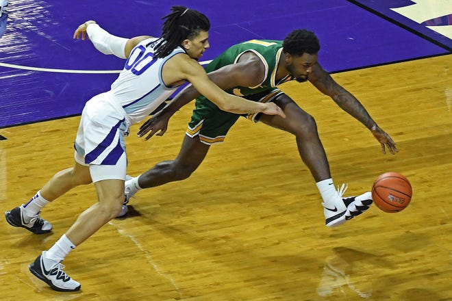 K-State Mike McGuirl (00) attempts to steal the ball against Jacksonville's Dontarius James (1) during Monday's game at Bramlage Coliseum.