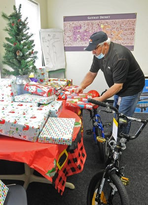 Randy Herbel, FedEx operations manager, rearranges the presents that were collected by 21 of the Salina FedEx employees to give to a family in need through the Catholic Charities Adopt-A-Family program this year.