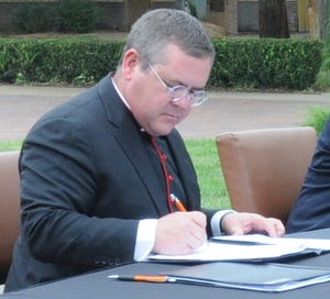 The Rev. Bobby Smith, president and dean of Saint Francis Ministries, signs merger paperwork uniting St. John's Military School and Saint Francis Ministries in 2019. The Kansas foster care leader charged $469,000 to credit cards and hid financial losses.