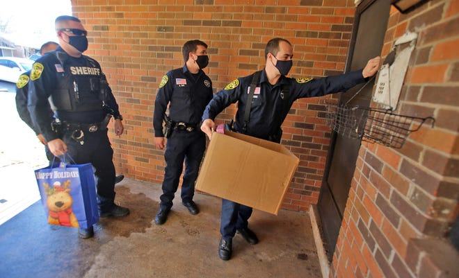 Sheriff's deputies knock on a door to deliver a box full of toys to a child in Kings Mountain on Monday.