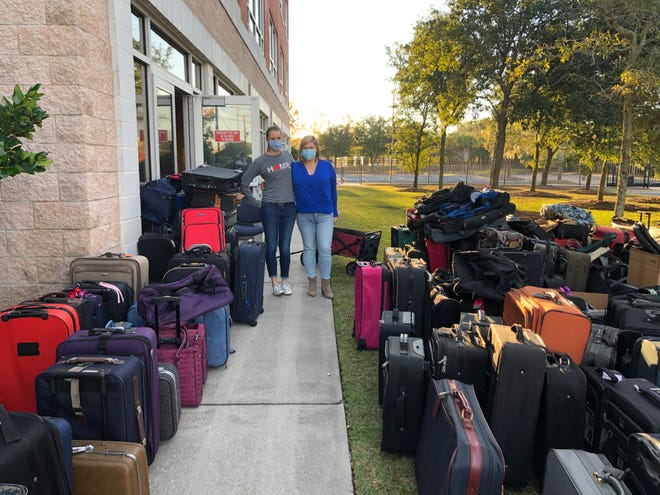 CASA Executive Director Kate Blair, left, poses with Jenny Rutherford of Jenny Rutherford Real Estate, who organized the collection of over 400 suitcases for foster children. [Photo courtesy Jenny Rutherford Real Estate]