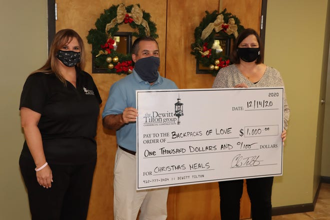 From left, Dewitt Tilton Group's Director of Operations Kim Thomas and Co-Principal Chris Tilton present $1,000 to Melodie Lane, director of Backpacks of Love.