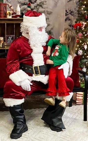 A little girl talks with Santa.