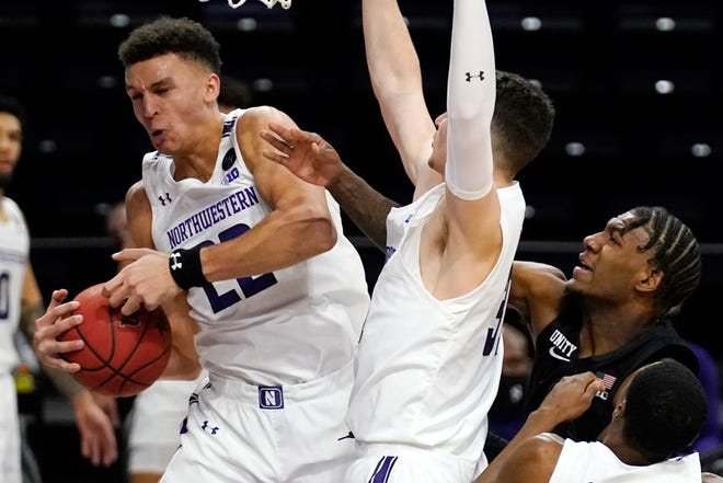 Northwestern forward Pete Nance, left, rebounds the ball against forward Robbie Beran, center, and Michigan State forward Aaron Henry  in Evanston on Sunday.