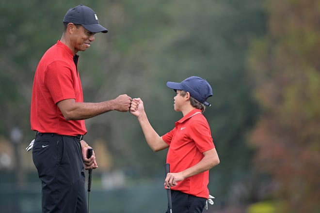 Tiger Woods, left, shares a fist-bump with his son Charlie after putting on the 18th green during the final round of the PNC Championship golf tournament, Sunday, in Orlando, Fla.