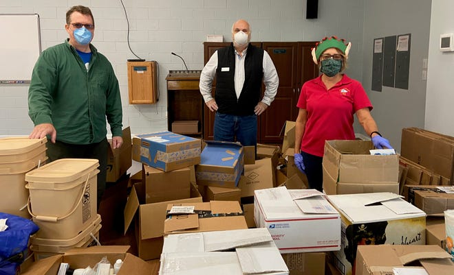 Doug King, Dave Phipps, and Carol Frysiek were some of the Yacht Club members who helped collect and sort food for the Commodores' Food Drive. [CONTRIBUTED PHOTO]