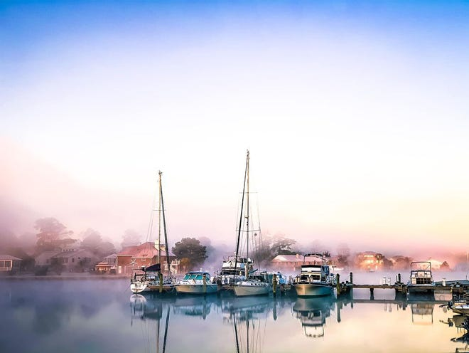This photo of the Shoreline Marina in Fairfield Harbour, taken by Bridgett Baysden on December 3, captures the beauty of Fairfield Harbour's Inner Harbour at the Shoreline Marina.  Although Bridgett is a professional photographer with the business name The Bee Hive, she did not have her camera with her that morning when she took her daughter to the bus stop. She noticed how pretty the fog was and snapped this photo with her cell phone. The result was spectacular! [CONTRIBUTED PHOTO]