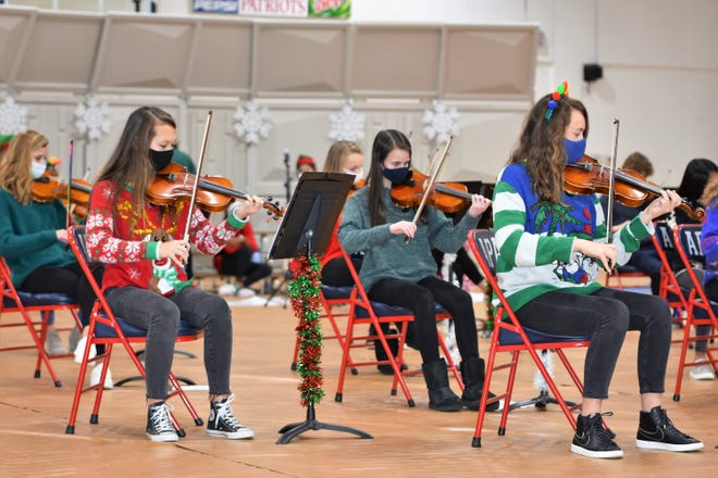 Picture, from left, violinist Hannah Henderson of New Bern, along with Mary Frances Fields and Chloe Albritton, serenade kindergarten students at Parrott Academy's Holiday Concert. [CONTRIBUTED PHOTO]