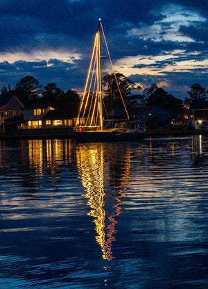 """On the balmy evening of December 12, residents gathered on the Shoreline Marina lawn or in their own backyards to enjoy the Holiday Parade of Lights sponsored by Fairfield Harbour Yacht Club. Sailboat masts were lighted for a beautiful vertical display and power boats were decked out in lights and other unique decorations.  A decorated rowboat, two paddleboards, and of course Santa joined the parade. It was truly a feast for the eyes. While the large crowd on the shore was waiting for the flotilla to come by, children sang """"Rudolph the Red Nose Reindeer"""" and other familiar carols. The flotilla provided an opportunity for neighbors to see each other from a safe distance and enjoy the festivities. The event was organized by Dave Pfefferkorn, who also doubled as Santa, and Phil Katz. It was a wonderful way to bring in the holiday season; many residents topped it off by driving around and enjoying the decorations on land as well as those they had just witnessed on sea. Photo is through the courtesy of Bob Dumon.[CONTRIBUTED PHOTO]"""