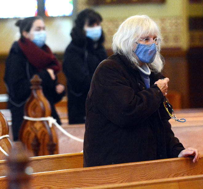 Nancy Demorest of Colchester makes the sign of the cross Monday during the noon Mass at the Cathedral of St. Patrick in Norwich. See more photos at NorwichBulletin.com