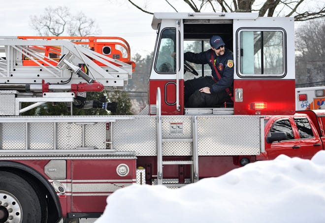 A Worcester Fire Department tillerman on Ladder 2 guides a truck out of Birch Hill Road after a call.