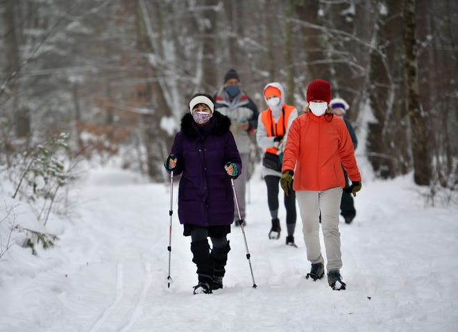 Hikers, some wearing snowshoes, head toward the Midstate Trail trail Monday in Rutland.