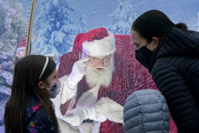 Santa talks to a family wearing masks as he sits inside a protective bubble in Seattle's Greenwood neighborhood on Dec. 8.