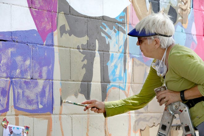 Artist Pam Valcante, an art teacher at Eastside High School, works on her mural that is part of the city of Gainesville's 5th Avenue Wall Project at Springhill on May 19.