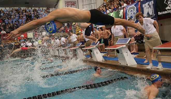 Gahanna Lincoln's Derek Yu dives into the pool as he swims the third leg of the 200-yard freestyle relay during the Division I state swimming preliminaries in Canton on Feb. 21.