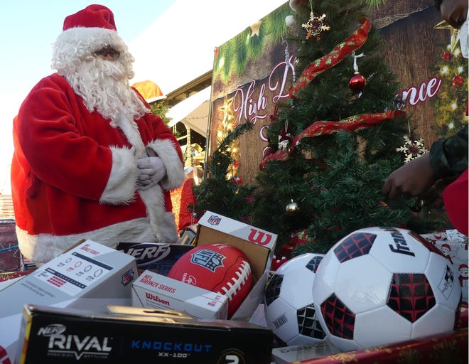 Santa and his volunteer elves helped High Desert Second Chance hand out hundreds of toys and boxes of food during its drive-through giveaway on Saturday in Hesperia.