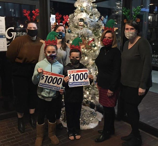 Cummings Properties designers Larissa Thoin and Brooke DeYoung, Brenna Barile, Michael Barile, receptionist Linda Curtis and designer Lauren Kirkness celebrate $5,000 in donations to Children's Hospital.