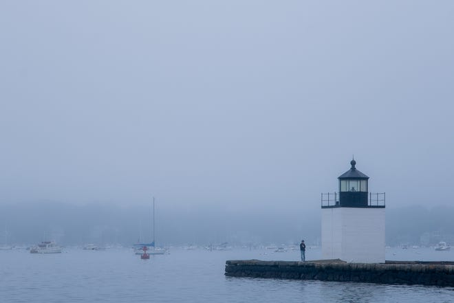 Among  The Salem Gazette's best photographs of 2020 depicts a person standing near the Derby Wharf Lighthouse in a thick fog on the morning of Sunday, Sept. 28, 2020.