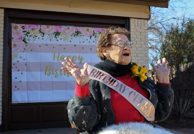 Helen Elkins reacts to a well-wisher's comment from the end of her driveway as she celebrated her 90th birthday Sunday afternoon with a drive-up party to her home.