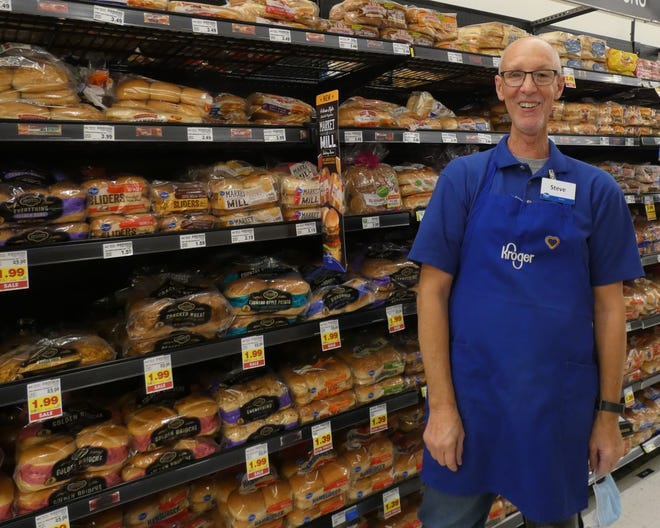 """Steve Dishon stands in the bread aisle, where he spends most of his work days at Kroger. He agreed to remove his mask briefly for a portrait. """"Without the mask, no one will know me now,"""" he said."""