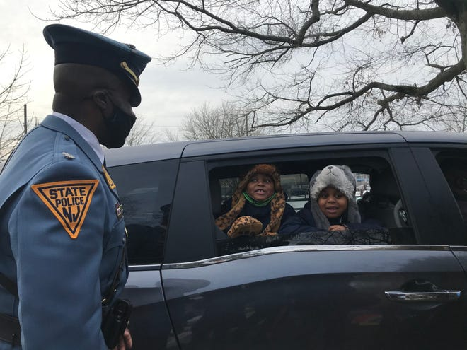 New Jersey State Trooper Fritz Fragé greets children at a toy giveaway in Camden on Monday.