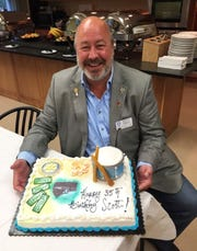 """Robert """"Scott"""" Darrah cracks a smile at a Rotary Club event while posing with a birthday cake presented in his honor. The longtime Rotarian died in early November at age 57 as a result of COVID-19 complications."""