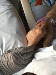 Nonie Dewell and husband, Larry, hold hands during his final days.