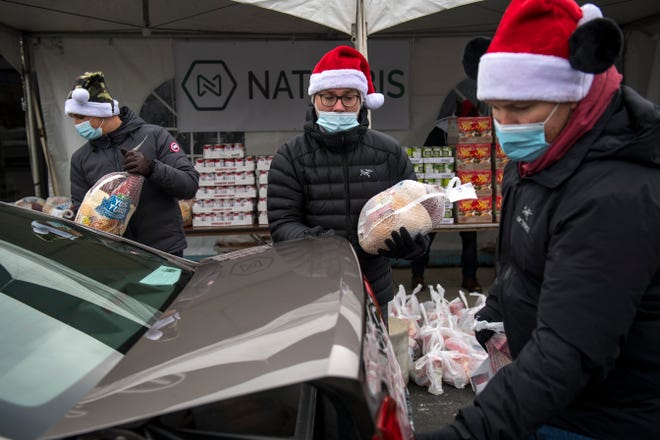 From left, Ben Puraj of Shelby Township, Nick Simpson of Washington Township and Mike Thomas of Washington Township deliver food to a vehicle during the drive through Christmas Dinner giveaway outside of Jim Brady's in Royal Oak, Mich on Dec. 21, 2020.