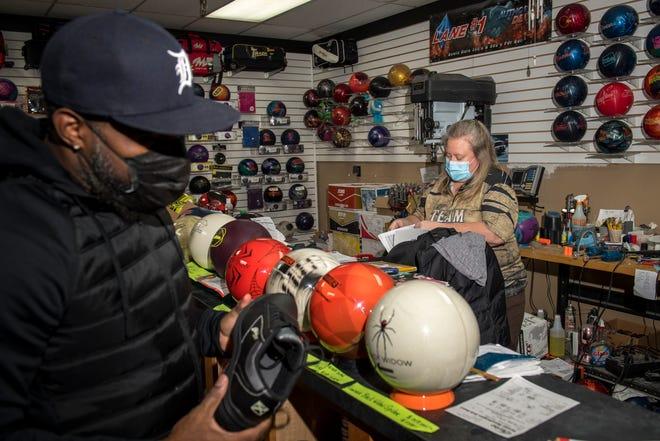 Lisa Bishop dari Redford, kanan, membantu Corey Smith dari Canton di toko bowling di Vision Lanes di Westland, Senin. Smith adalah pelanggan pertama di dalam toko setelah dibukanya kembali arena bowling dan bioskop Michigan pada 21 Desember 2020.