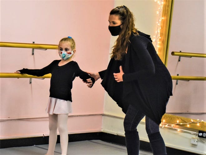 Kassandra Ringle helps a student pose at Kassandra's Dance Academy.