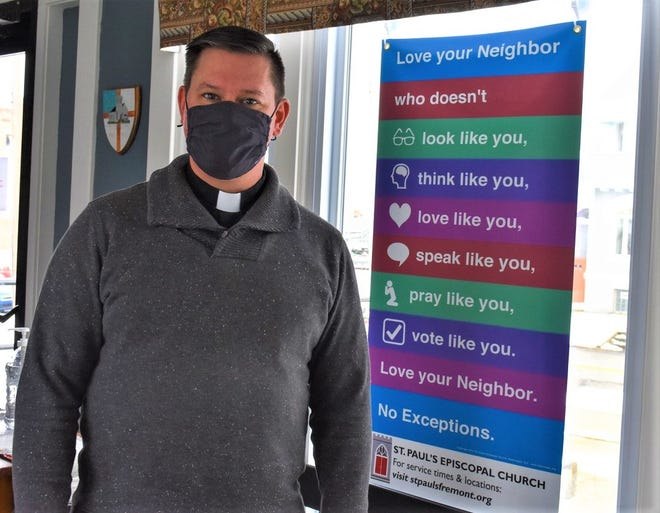 This Christmas, Rev. Matt Wahlgren of St. Paul's Episcopal Church reminded his congregation that when Christ put on humanity, he chose to be defined by love and vulnerability. Here, Wahlgren stands next to a sign inside the church which encourages the congregation to love others fully, without exception.