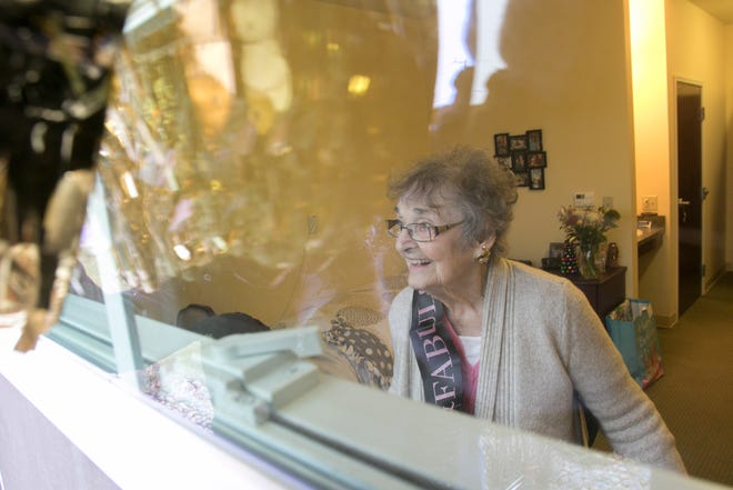 100-year-old Bernie Coles looks out her window in her room at the Willows at Howell Monday, Dec. 21, 2020 at her children and grandchildren who have assembled outside to wish her a happy 100th birthday.