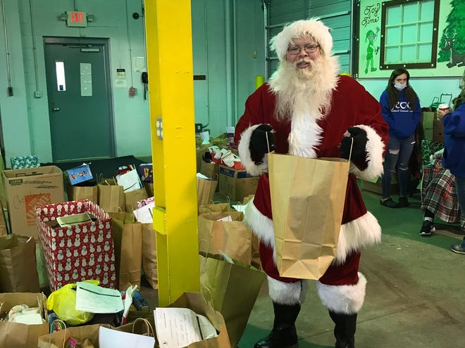Santa, also known as volunteer Charlie Justice, Saturday helped to deliver Christmas gifts to 390 children who come to the Richland Outreach Center, now located at their new home in the former Toy Time building at 280 N. Diamond St.