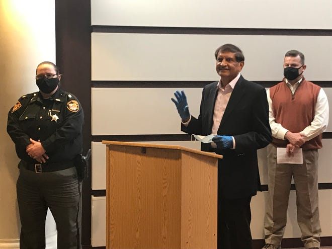 Dr. Dalsukh Madia (middle) gives a statement about a donation he and his wife made to Marion Police Officers at the Marion County Building on Dec. 19, 2020.