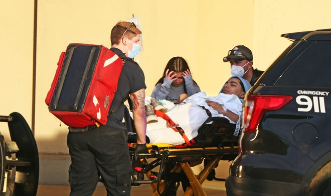 An unidentified man is transported at Mayfair mall after a multiple shooting inside the mall on Friday, Nov. 20, 2020. Several victims were injured and taken to hospitals.