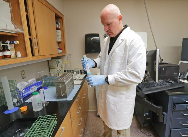 Greg Wallace, lead forensic toxicologist, uses an elution solvent to determine the amount of a drug in a person's system in the toxicology lab at the Milwaukee County Medical Examiner's Office.