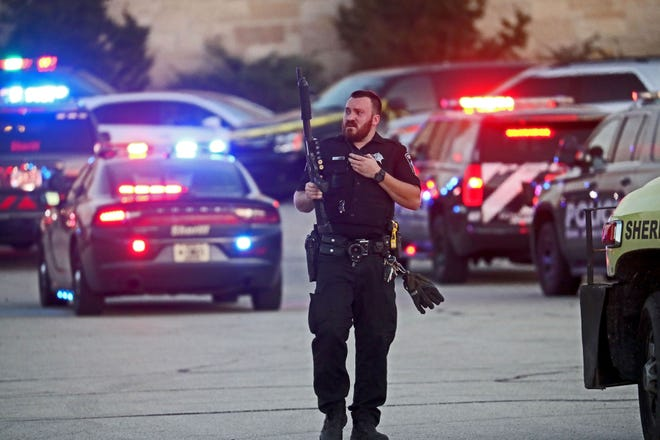 A Milwaukee County sheriff's deputy with a shotgun heads back to his vehicle in the parking lot of Mayfair mall in Wauwatosa, where multiple people were shot on November 20, 2020.