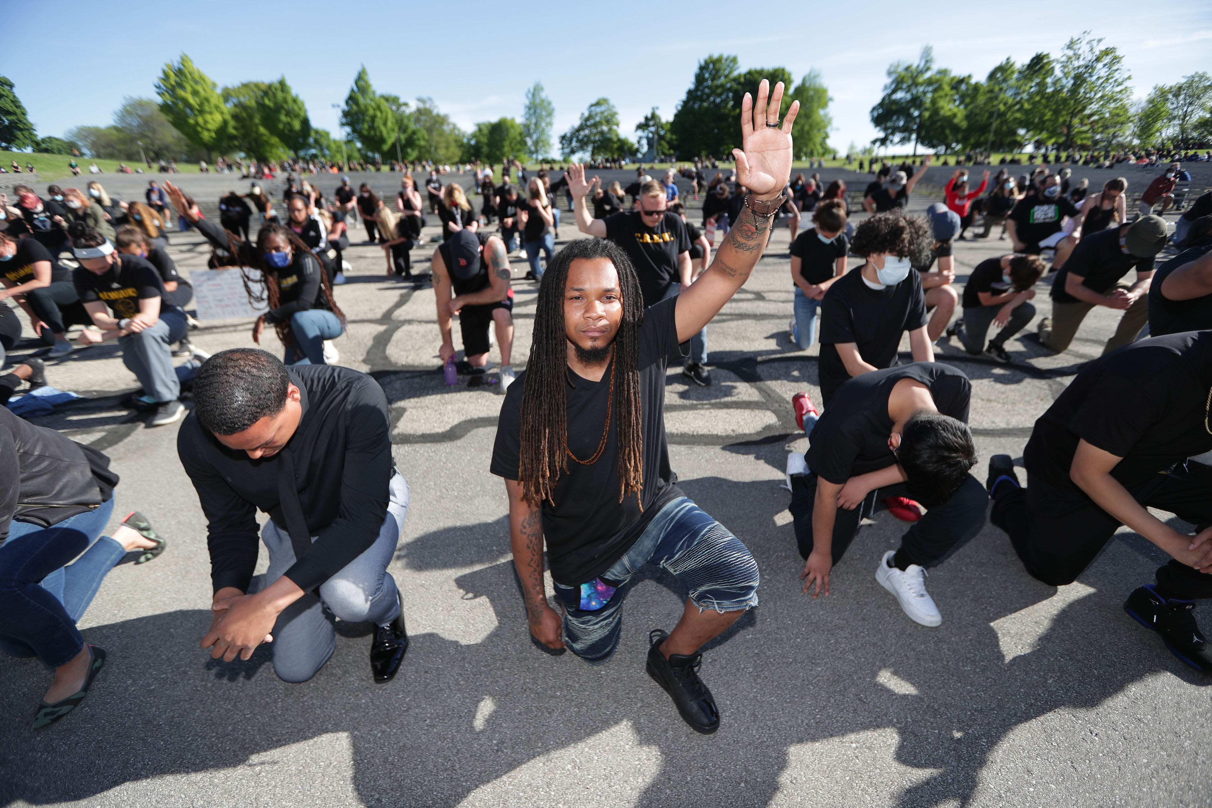 Terry Thompson, center, with Salt and Light Christian group from Oak Creek Assembly of God church, is joined by others as they take a knee, the opposite knee the Minneapolis officer used in the death of George Floyd, showing support against police brutality during a peaceful prayer protest at Washington Park on Sunday, May 31, 2020.