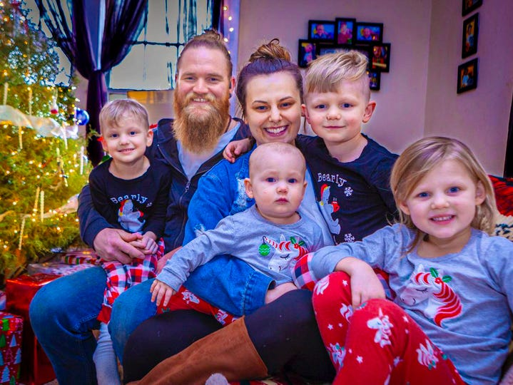 Dustin and Ashley Dailey, center, hold children, from left,  4-year-old Reid, 5-year-old Zayne, 1-year-old Lyla and 4-year-old Ryleigh, of Murfreesboro. The family is featured in a Trace Adkins video, 'Ain't That Kind of Cowboy,' which debuted in December.