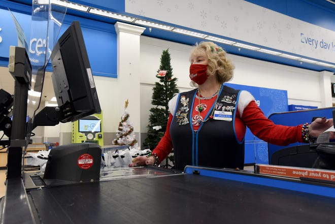 """Vanessa Lawson, better known as """"Jingles"""" in December, helps a customer check out in her signature bells while working on Monday, Dec. 21, 2020 at the Walmart in Newark."""