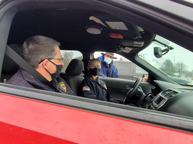 South Lyon Fire Chief Robert Vogel and Sgt. Cindy Conrad wait in their vehicle during a 15-minute observation period after receiving the first dose of their COVID-19 vaccination as Oakland County Medical Director Russell Faust looks on at the Waterford Regional  Fire Department Headquarters, Dec. 18, 2020.