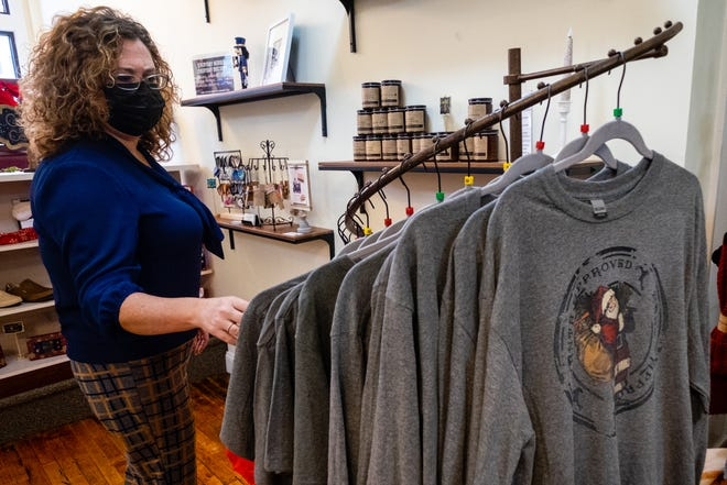Jorja Baldwin, owner of District 43 in downtown Port Huron, looks at locally-made shirts Monday, Dec. 21, 2020, in her downtown store.
