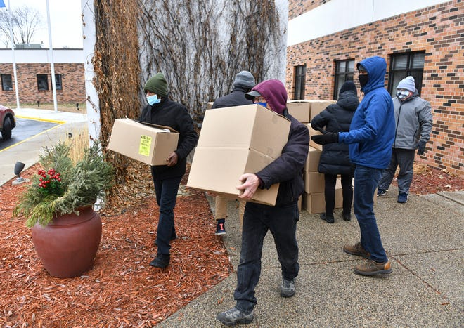 Volunteers distribute boxes of food as part of a Feeding Area Children Together drive Monday, Dec. 21, 2020, at Atonement Lutheran Church in St. Cloud.