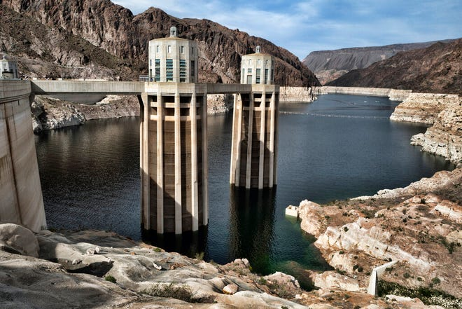 FILE - This March 26, 2019, file photo, shows a bathtub ring of light minerals showing the high water mark of the reservoir which has shrunk to its lowest point on the Colorado River, as seen from the Hoover Dam, Ariz. A set of guidelines for managing the Colorado River helped several states through a dry spell, but it's not enough to keep key reservoirs in the American West from plummeting amid persistent drought and climate change, according to a U.S. report released Friday, Dec. 18, 2020. (AP Photo/Richard Vogel, File)