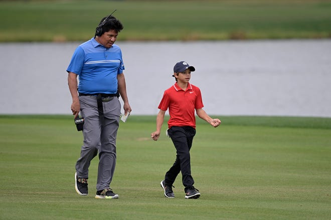 Golf Channel and NBC on-course analyst Notah Begay, left, talks with Charlie Woods, son of golfer Tiger Woods, as they walk on the 18th fairway.