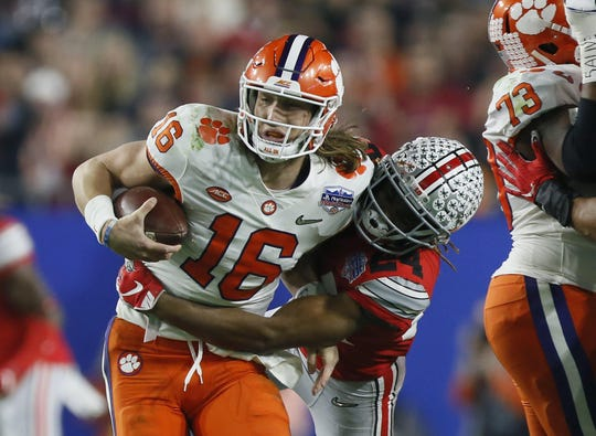 Clemson quarterback Trevor Lawrence is tackled by Ohio State cornerback Shaun Wade in the Fiesta Bowl.