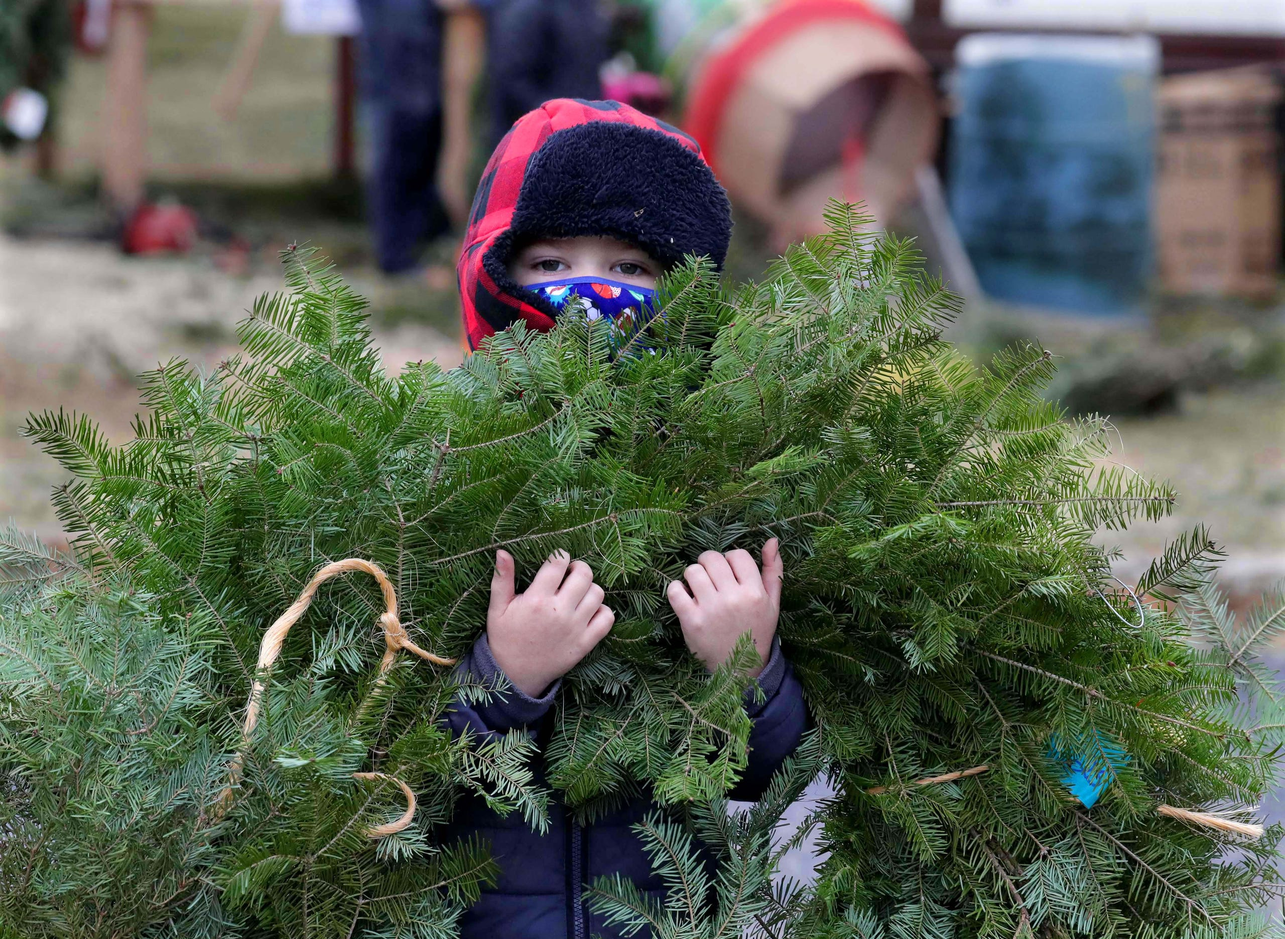 Nicholas Kleinmann, 4, carries a wreath to his parents' vehicle at the Ideal Christmas Trees lot on North Santa Monica Boulevard in Whitefish Bay, Wis. on Sunday, Dec. 6, 2020.