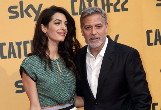 """George Clooney, right, seen with his wife, Amal Clooney, at a 2019 premiere, says Amal is watching """"ER"""" episodes and is not impressed with the behavior of his character, Dr. Doug Ross."""